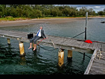 Sitting on the dock of the bay. Business man in business attire on the dock of the bay, with bare feet, a fishing rod bench and relaxing as he reels in his next royalty free stock photos