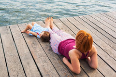 Sitting on a dock. Mother and child sitting on a lakeside dock relaxing Stock Photo