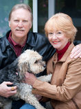 Sitting with the dog. Happy retired couple embracing one another retired couple sitting with their dog Royalty Free Stock Photography