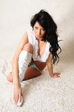 Sitting Down. Female model sitting on the floor wearing fashionable clothing and looking directly at the camera Stock Photos