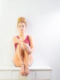 Sitting On Dresser di modello femminile americano sbalorditivo Fotografia Stock