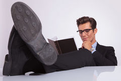Sitting with feet on desk & reading Stock Photos