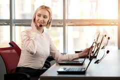 Sitting female call center operator looking back. Gaze of adorable adult female operator. Bright windows background Royalty Free Stock Photos