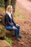 Sitting female hiker waiting by the side of the road Stock Photos