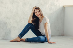 Sitting on the floor. Beautiful girl sitting on the floor Royalty Free Stock Photography