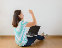 Sitting on the floor with a laptop raising his arms with a look Royalty Free Stock Images
