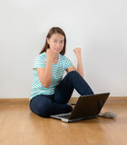 Sitting on the floor with a laptop raising his arms with a look Stock Images