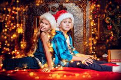 Sitting on the floor. A portrait of children sitting on the floor together. Merry Christmas, happy New Year. Luxurious apartment with a christmas tree, lights royalty free stock photos