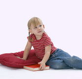 Sitting on floor, on red pillow little girl Stock Photos