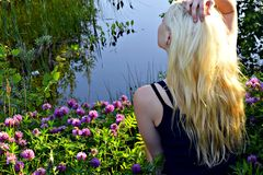Sitting on a floral carpet of clover near the forest of a small lake blond girl Stock Photos