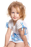 Sitting girl. Little girl in a white dress sits and looks into the camera Stock Photography
