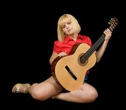 Sitting girl with acoustic guitar Stock Images