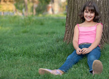Sitting girl against the tree Royalty Free Stock Photography