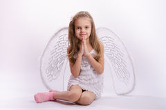 Sitting girl in an angel costume with folded hands Royalty Free Stock Images