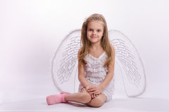 Sitting girl in an angel costume on a white background. Six year old girl in a bright angel costume with wings on a white background Royalty Free Stock Photos