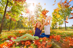 Sitting girl and boy play with leaves in forest Stock Photography