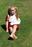 Sitting girl with broken hand. Barefoot girl in red dress with broken hand sitting on the grass stock image