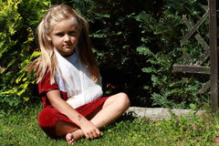 Sitting girl with broken hand. Barefoot girl in red dress with broken hand sitting on the grass royalty free stock photos