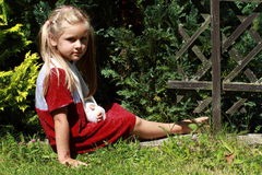 Sitting girl with broken hand. Barefoot girl in red dress with broken hand sitting on the grass stock photography