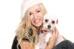 Sitting girl cuddling a dog. A sitting female hugging a small white dog Stock Image
