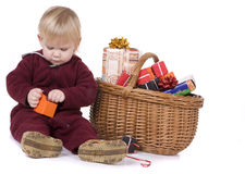 Sitting girl with gift boxes in wicker basket Stock Images