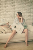Sitting girl with guitar. Blonde girl sitting on a couch with a guitar Royalty Free Stock Photos