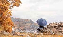 Sitting girl holding an umbrella Royalty Free Stock Photography