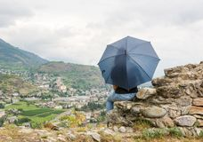 Sitting girl holding umbrella on a wall Stock Image