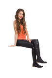 Sitting Girl Isolated. Smiling young woman in black leather trousers, orange shirt and boots sitting on white space and looking at camera. Side view, Full length Royalty Free Stock Images