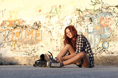 Sitting girl with roller skates on graffiti background Royalty Free Stock Images