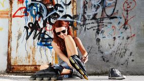 Sitting girl with roller skates on graffiti background stock footage