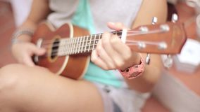 Sitting girl in shorts playing ukulele guitar on street. Summer sunny day. Music. Strings. Sound. Sitting girl in shorts playing brown ukulele guitar on street stock footage