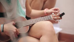 Sitting girl in shorts tune brown ukulele guitar on street. Summer sunny day. Music. Strings. Sound stock video
