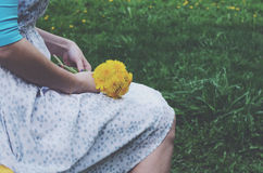 Sitting girl in vintage dress holding bunch of yellow dandelions Stock Images