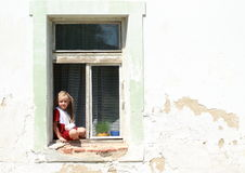 Sitting girl in a window with broken hand. Girl in red dress with broken hand sitting in the window stock images