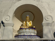 Sitting Golden Buddha. A sitting golden buddha on the left hand side of the Peace Pagoda located in leverett, massachusetts Stock Photo