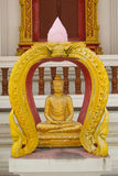 Sitting golden buddha statue in front of the church . Royalty Free Stock Photo