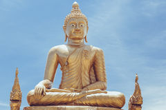 Sitting golden Buddha statue in Thailand over sky Stock Photography