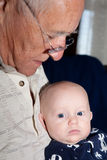 Sitting Grandpa's Lap. Baby sitting on his grandfather's lap. Image orientation is vertical Stock Image
