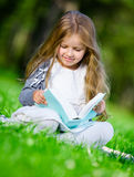 Sitting on the grass girl reads book Stock Photos