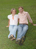 Sitting in the Grass Together. A couple enjoys the out of doors in a green, grassy field Royalty Free Stock Photography