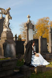 Sitting on a grave. Victorian girl sitting on a grave and holding roses Royalty Free Stock Photos