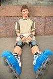 Sitting guy in rollerblades Stock Images