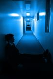 Sitting in hallways. A man sitting in a blue hallway Stock Images