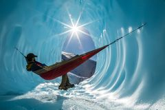 Sitting in a hammock inside the entrance of an ice cave in a glacier in Alaska. Deep in the Alaskan wilderness, an ice climber rests in a hammock set up in the royalty free stock photography