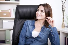 Sitting Happy Businesswoman with Hand on her Hair stock images