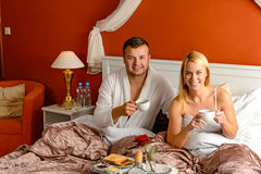 Sitting happy husband wife bed drinking tea Royalty Free Stock Images