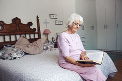 Sitting on her bed reading a book Royalty Free Stock Photos