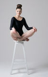 Sitting on a high chair. Girl in black gymnastyc leotard is sitting on the high white chair Stock Photography