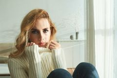 Sitting at home on cold winterday. Portrait of beautiful young woman in white warm sweater Royalty Free Stock Photos